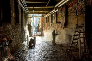workers cleaning graffiti from concrete walls
